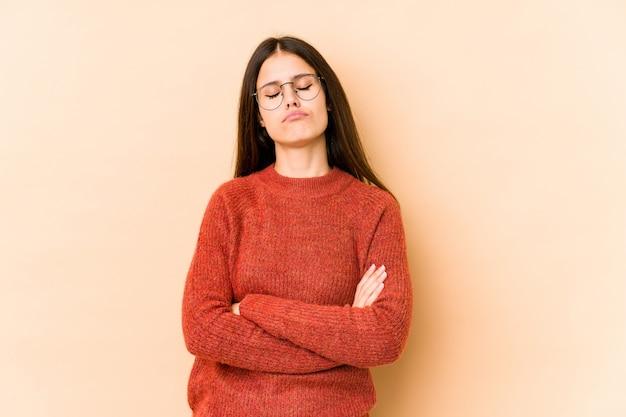 Jovem mulher caucasiana isolada na parede bege cansada de uma tarefa repetitiva.
