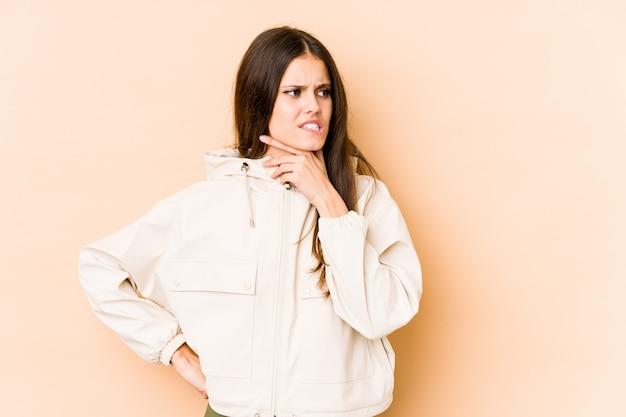 Jovem mulher caucasiana isolada na parede bege tocando a parte de trás da cabeça, pensando e fazendo uma escolha.