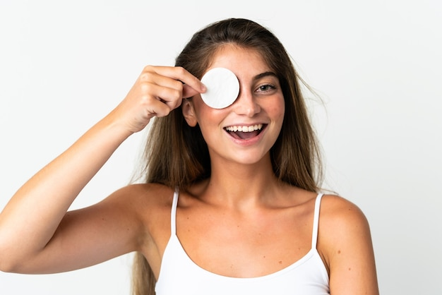 Jovem mulher caucasiana isolada na parede branca com algodão para tirar a maquiagem do rosto e sorrindo