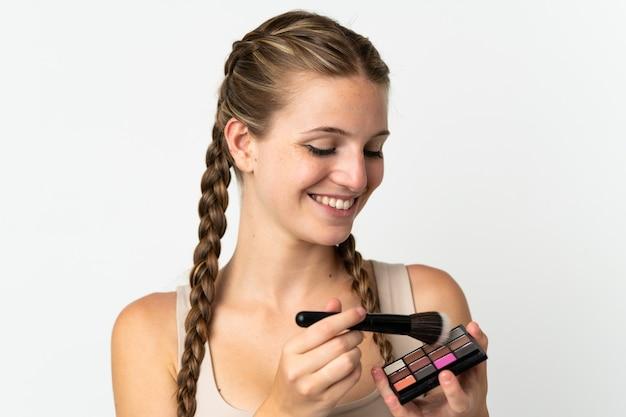 Jovem mulher caucasiana isolada na parede branca com paleta de maquiagem