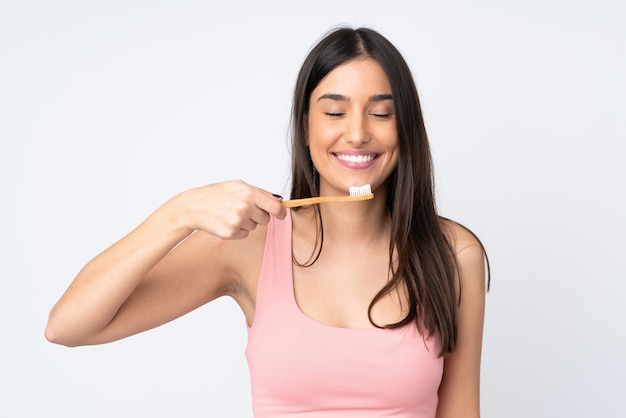 Jovem mulher caucasiana isolada na parede branca com uma escova de dentes e uma expressão feliz