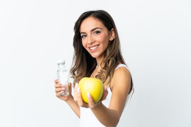 Jovem mulher caucasiana isolada na parede branca com uma maçã e uma garrafa de água