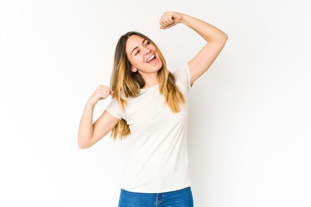 Jovem mulher caucasiana, isolada na parede branca comemorando um dia especial, pula e levanta os braços com energia.