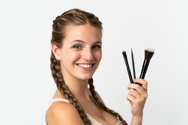 Jovem mulher caucasiana isolada na parede branca segurando um pincel de maquiagem