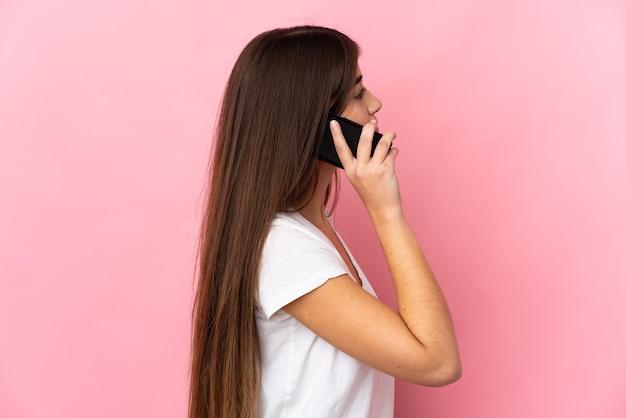 Jovem mulher caucasiana isolada na parede rosa, conversando com alguém ao telefone celular