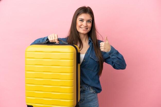 Jovem mulher caucasiana isolada na parede rosa em férias com mala de viagem e polegar para cima