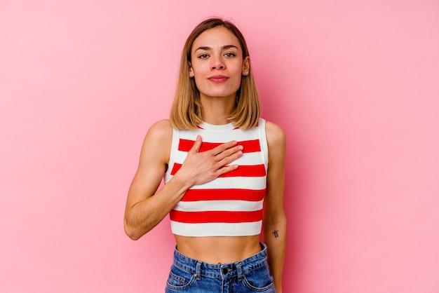 Jovem mulher caucasiana isolada na parede rosa, fazendo um juramento, colocando a mão no peito.