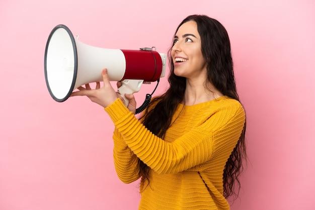 Jovem mulher caucasiana isolada na parede rosa gritando em um megafone para anunciar algo