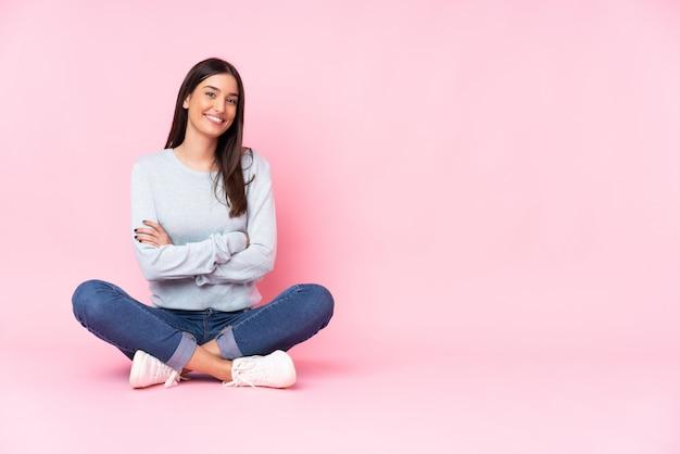 Jovem mulher caucasiana isolada na parede rosa, mantendo os braços cruzados na posição frontal