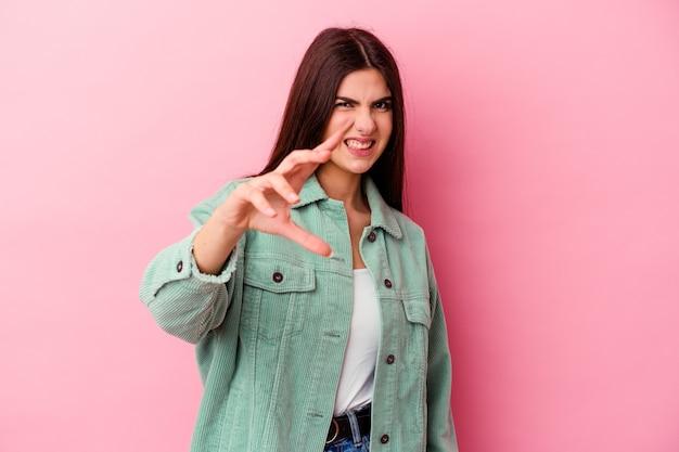 Jovem mulher caucasiana isolada na parede rosa mostrando garras imitando um gato, gesto agressivo