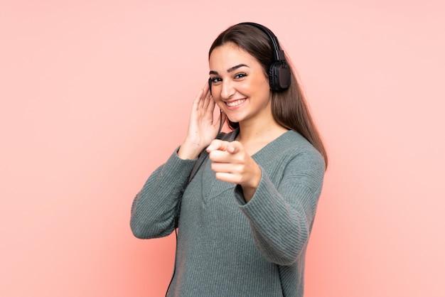 Jovem mulher caucasiana isolada na parede rosa, ouvindo música e apontando para a frente