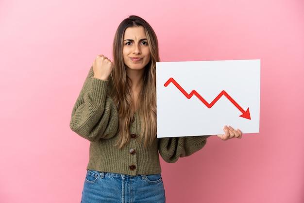 Jovem mulher caucasiana isolada na parede rosa segurando uma placa com um símbolo de seta de estatísticas decrescentes e com raiva