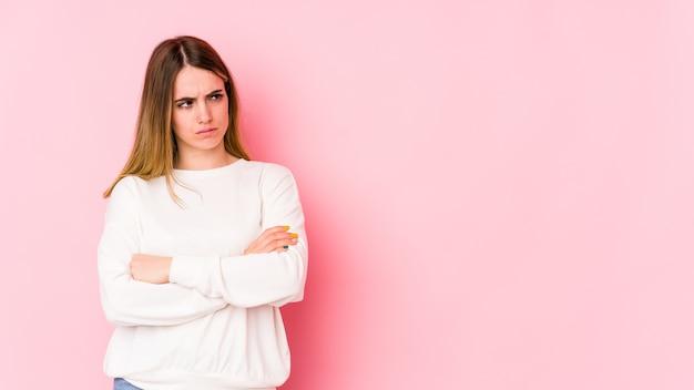 Jovem mulher caucasiana isolada na parede rosa suspeita, incerta, examinando você.