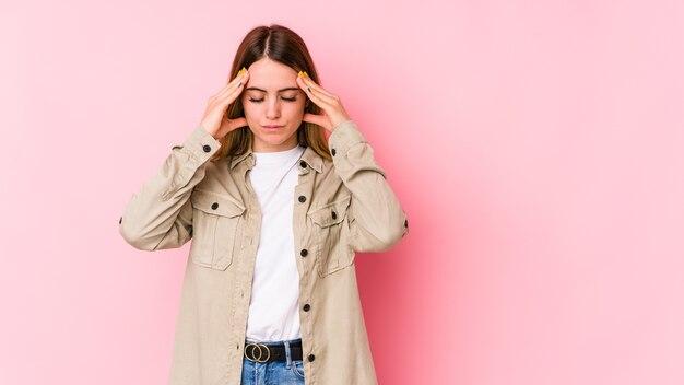 Jovem mulher caucasiana isolada na parede rosa, tocando as têmporas e tendo dor de cabeça.