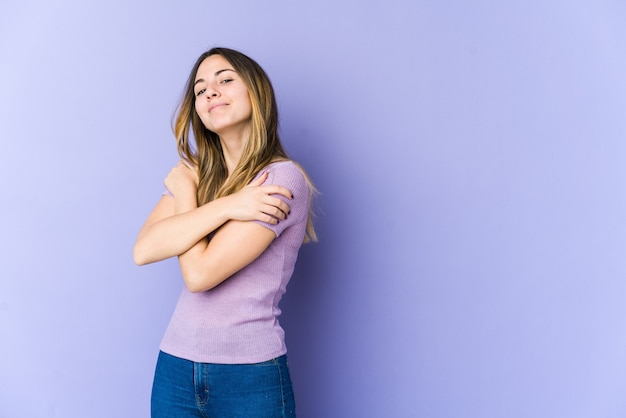 Jovem mulher caucasiana isolada na parede roxa abraços, sorrindo despreocupada e feliz.