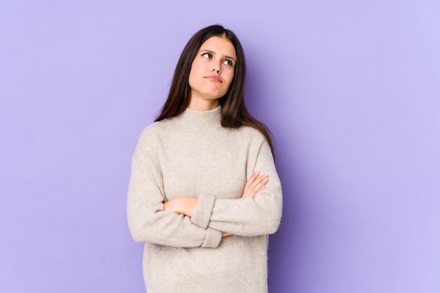 Jovem mulher caucasiana isolada na parede roxa cansada de uma tarefa repetitiva.