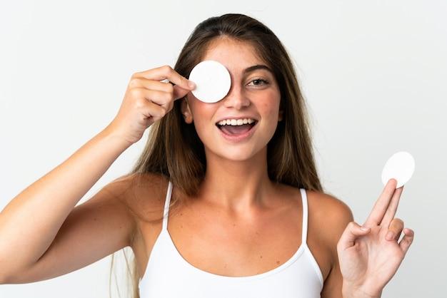 Jovem mulher caucasiana isolada no branco com almofada de algodão para remover a maquiagem do rosto e sorrindo