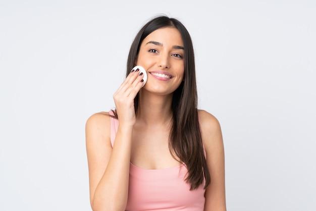 Jovem mulher caucasiana isolada no branco com almofada de algodão para remover a maquiagem do rosto