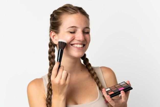 Jovem mulher caucasiana isolada no branco com paleta de maquiagem e feliz