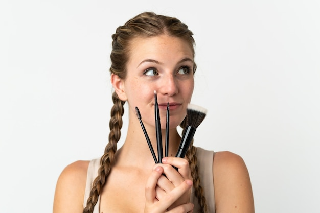 Jovem mulher caucasiana isolada no branco segurando um pincel de maquiagem e olhando para cima