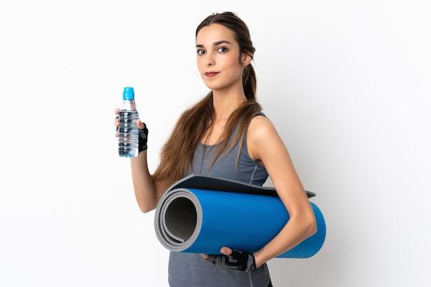 Jovem mulher caucasiana isolada no fundo branco com garrafa de água esportiva e um tapete
