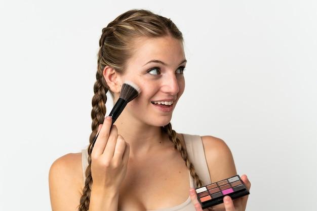 Jovem mulher caucasiana isolada no fundo branco com paleta de maquiagem e feliz