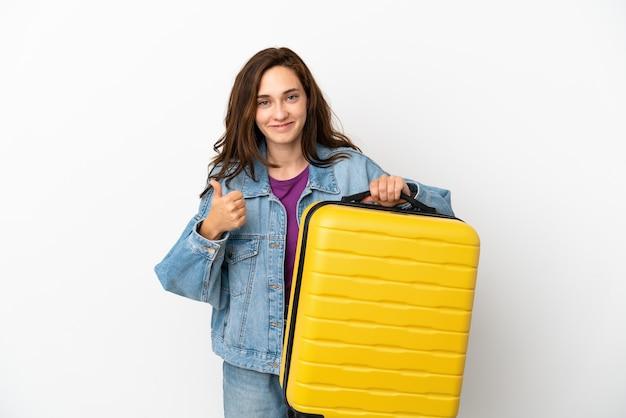 Jovem mulher caucasiana isolada no fundo branco de férias com mala de viagem e polegar para cima
