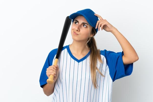 Jovem mulher caucasiana isolada no fundo branco jogando beisebol e tendo dúvidas com a expressão facial confusa