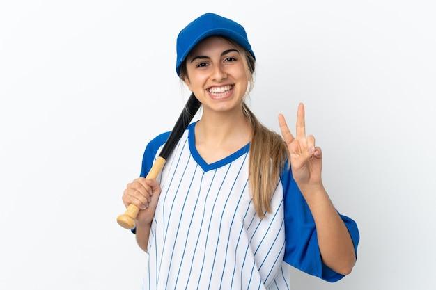 Jovem mulher caucasiana isolada no fundo branco jogando beisebol, sorrindo e mostrando o sinal da vitória