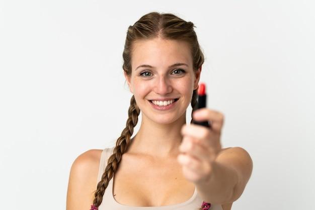 Jovem mulher caucasiana isolada no fundo branco segurando batom vermelho e oferecendo-o