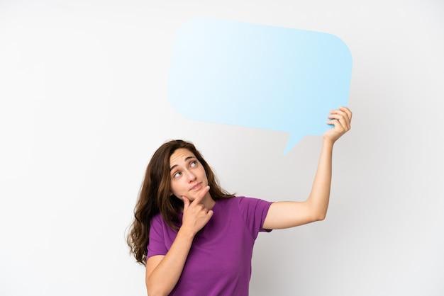 Jovem mulher caucasiana, isolada no fundo branco, segurando um balão de fala vazio e pensando Foto Premium