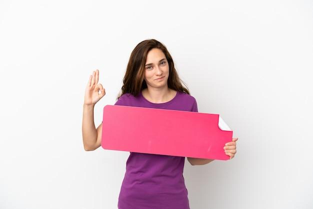 Jovem mulher caucasiana isolada no fundo branco segurando um cartaz vazio e fazendo sinal de ok