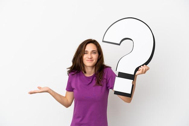 Jovem mulher caucasiana isolada no fundo branco segurando um ícone de ponto de interrogação e tendo dúvidas