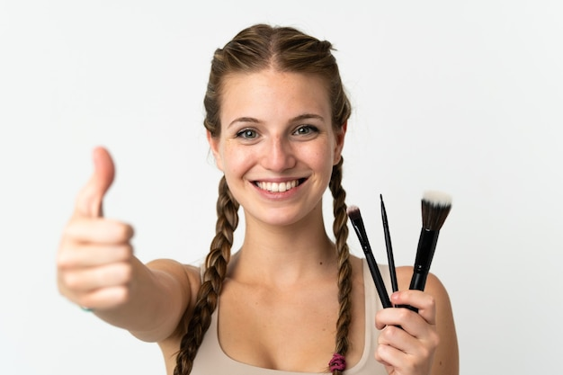 Jovem mulher caucasiana isolada no fundo branco segurando um pincel de maquiagem e com o polegar para cima