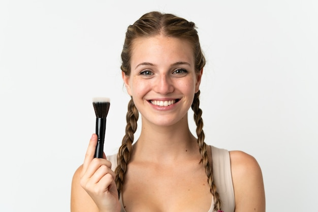 Jovem mulher caucasiana isolada no fundo branco segurando um pincel de maquiagem e uma expressão feliz.