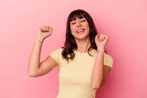 Jovem mulher caucasiana isolada no fundo rosa, dançando e se divertindo.