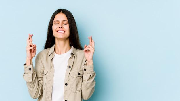 Jovem mulher caucasiana isolada nos dedos de cruzamento de parede azul por ter sorte