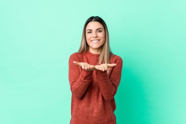 Jovem mulher caucasiana isolada segurando algo com as palmas das mãos, oferecendo à câmera.
