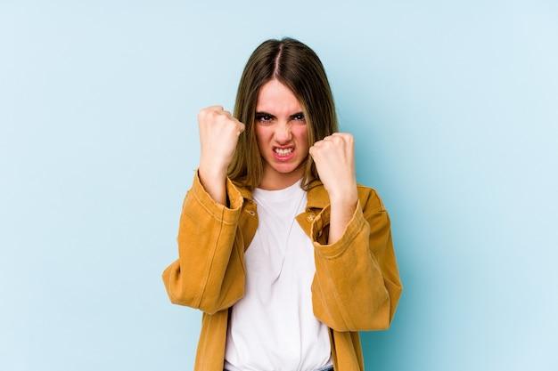 Jovem mulher caucasiana isolada sobre azul chateada, gritando com as mãos tensas.