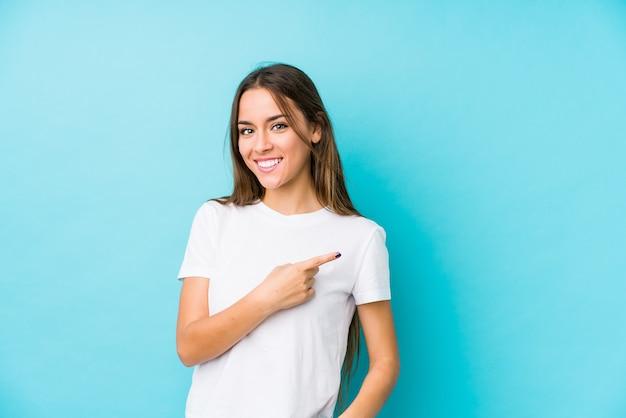 Jovem mulher caucasiana isolada sorrindo e apontando de lado, mostrando algo no espaço em branco.