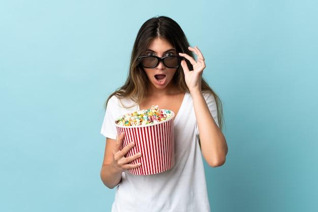Jovem mulher caucasiana isolada surpresa com óculos 3d e segurando pipoca