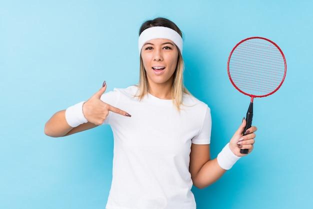 Jovem mulher caucasiana jogando badminton isolado pessoa apontando à mão para um espaço de cópia de camisa, orgulhoso e confiante