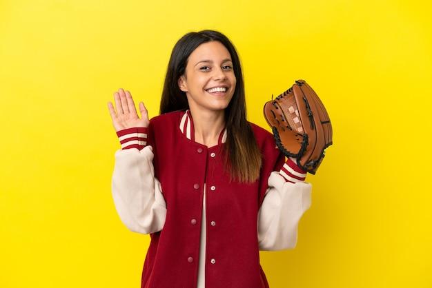 Jovem mulher caucasiana jogando beisebol isolado em um fundo amarelo, saudando com a mão com uma expressão feliz