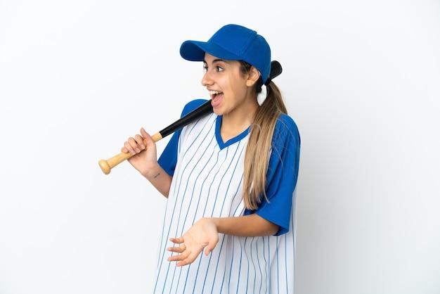 Jovem mulher caucasiana jogando beisebol isolado no fundo branco com expressão de surpresa enquanto olha para o lado