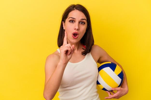 Jovem mulher caucasiana, jogando vôlei isolado em fundo amarelo, tendo uma ideia, o conceito de inspiração.