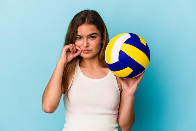 Jovem mulher caucasiana jogando vôlei isolado em um fundo azul com os dedos nos lábios, mantendo um segredo.
