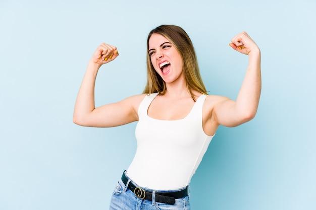 Jovem mulher caucasiana, levantando o punho após uma vitória, o conceito de vencedor. Foto Premium