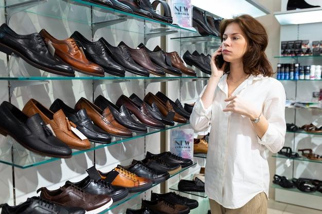 Jovem mulher caucasiana liga e aconselha sobre a compra de sapatos masculinos