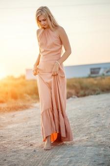 Jovem mulher caucasiana linda num vestido rosa caminha na areia com os pés descalços durante o pôr do sol