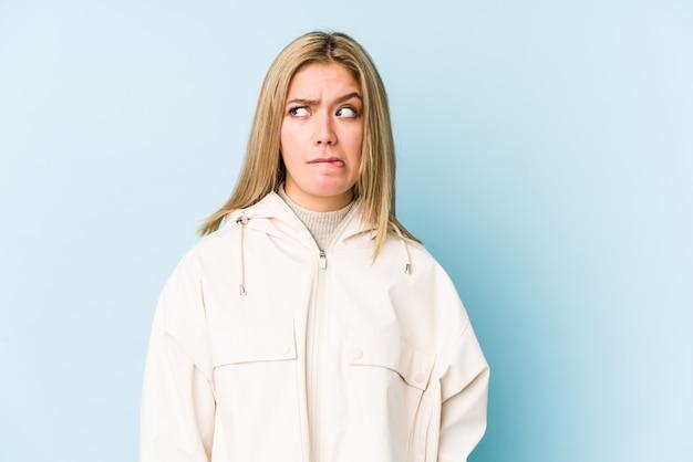 Jovem mulher caucasiana loira isolada confusa, sente-se duvidoso e inseguro.